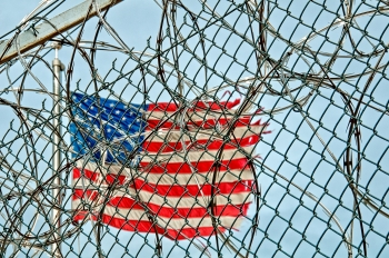 Picture of American flag behind barbed wire.