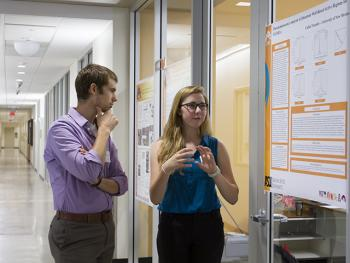 Cailin Treseder, a University of New Mexico student with a Research Experiences for Undergraduates pilot program, presents her research to assistant professor Zachary Holman in the summer of 2013.