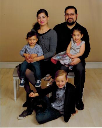 Rachel Hill, wearing a gray sweater and vivid pink lipstick, sits next to the right of her husband. They are each holding one of their children on their laps, and a third sits on the floor in front of them. They are posing for a family portrait.