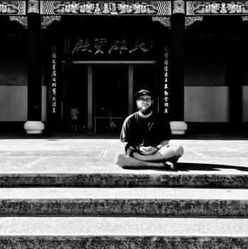 Nathaniel Harris sits in front of a temple