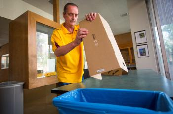 man putting cardboard into recycling bin