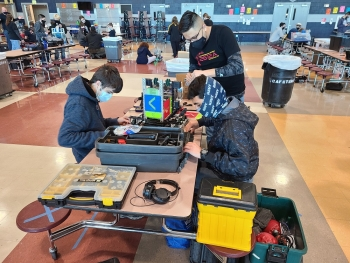 Three masked high school seniors work on a robot with four wheels at a table with tools strewn about