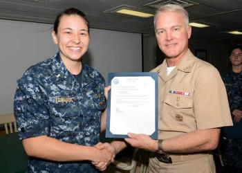 Vice Admiral Thomas Rowden awards Ensign Rachelle Edwards her surface warfare officer pin.