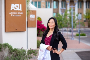 Samantha Casselman poses with her white nurse practitioner coat by ASU's Mercado Building on the Downtown Phoenix campus