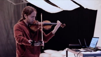 Instructor and violinist Seth Thorn holding his hybrid violin