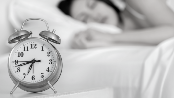 Alarm clock in the foreground with woman sleeping in the background