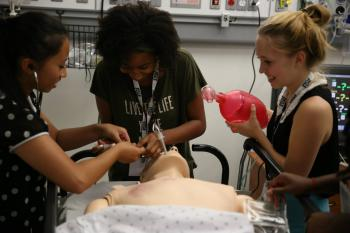 high school students practicing intubation on a dummy