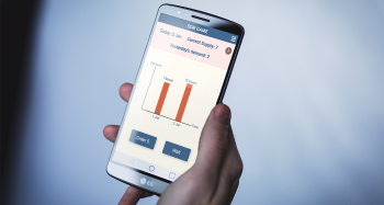 A hand holds a smart phone. On its screen is a app designed to educate users about supply chain management. The caption reads: Banner image: A rendering of the ShipShape app in use. Image courtesy of Luminosity