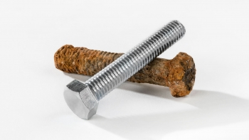 A rusty screw and a new screw show the destruction of corrosion on metal and metal alloys.