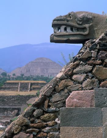 Carved jaguar head on the Temple of the Feathered Serpent, pyramid in background