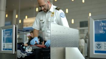 A TSA agent searches luggage at airport security checkpoint.