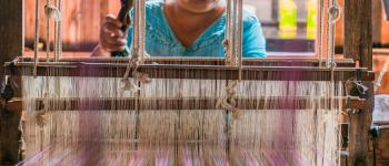 A woman weaves at a traditional loom