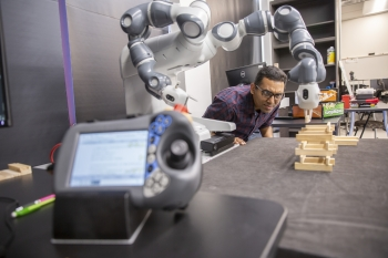 man working with a robot in a lab