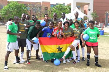 MasterCard Foundation Scholars pose with flags and soccer balls at charity event