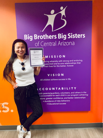 Sofia holding her award certificate in front of Big Brothers Big Sisters sign