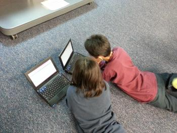 children lying on floor using laptop computers