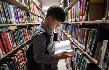 A student looks at book in Hayden Library bookshelves
