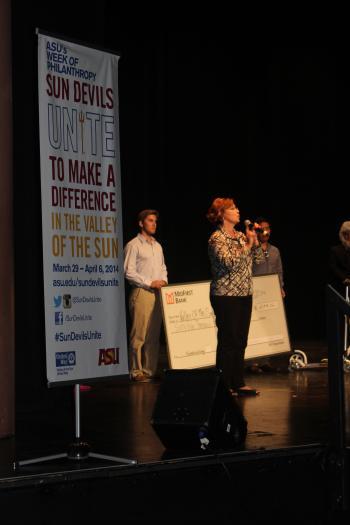 woman speaking on stage during Devils Unite Week of Philanthropy
