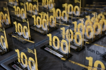 table full of glass awards featuring the number 100