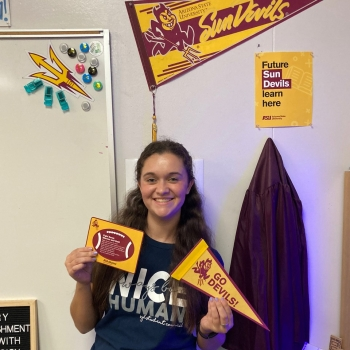 ASU alum and current teacher Jenna Brooks smiles and holds up some ASU-themed swag she received as part of a Sun Devil teacher pack.