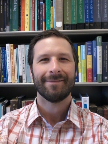 Portrait of ASU Professor C. Tyler DesRoches with books in background