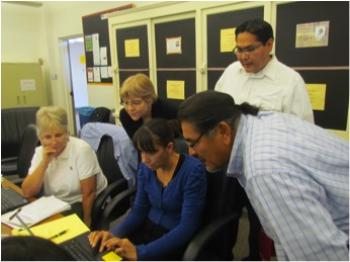 people looking over shoulder of woman on computer