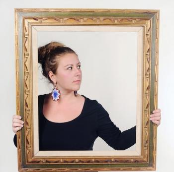 portrait of woman standing behind picture frame