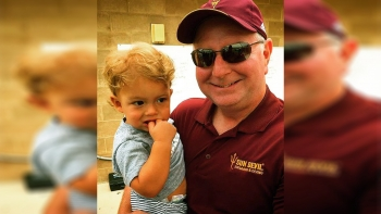 ASU swimming Coach Bob Bowman smiles as he holds Olympic swimmer Michael Phelps' son, Boomer Phelps