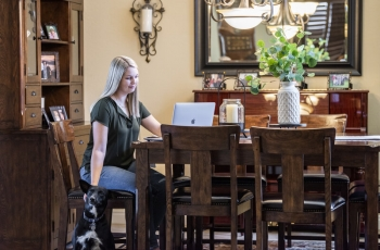 Woman at home on computer petting her dog
