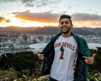 man wearing ASU Sun Devils jersey on a mountain with a city in the background