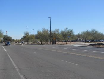 A wide street with a car in the distance driving toward the vantage point.