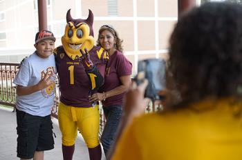 family getting picture taken with ASU mascot, Sparky