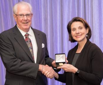 william yost receives the gold medal from ASA president marcia isakson