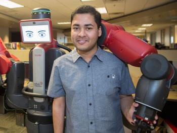 Computer science graduate student Tathagata Chakraborti and the Yochan lab robot Newman