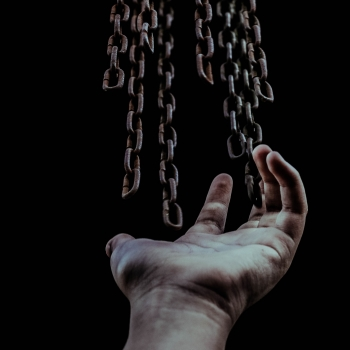 Hand breaking out of chains