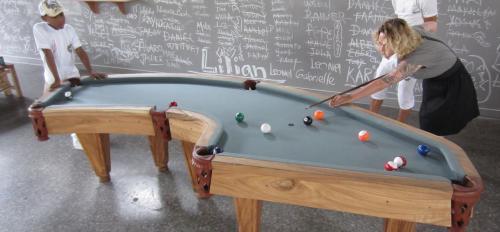 People playing on an irregular pool table.