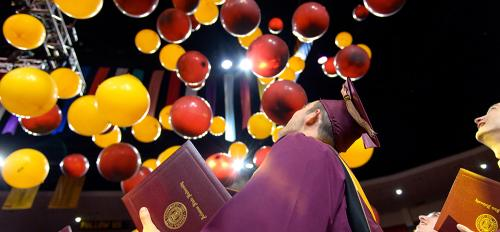 student looking at balloons during commencement