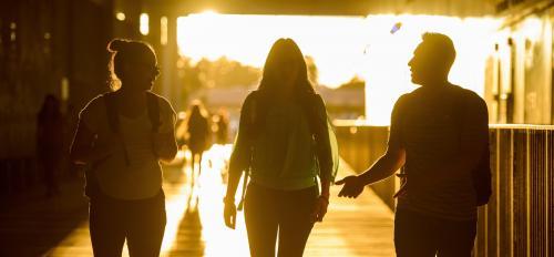 students walking at Coor Hall at sunset
