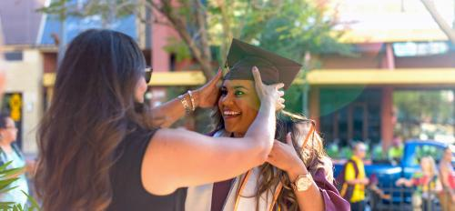 A graduate gets help adjusting her cap