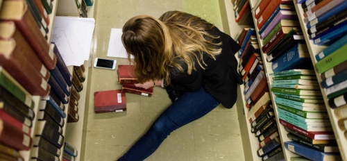 """Then-doctoral student Emily Zarka combs through books from Hayden Library's stacks looking for traces of the books past """"lives"""" in this 2017 photo from the ASU Book Traces project. Photo by Andy DeLisle/ASU."""