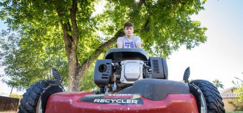 Bryson Leander mows the yard