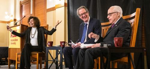 A women and two men sit on a stage for a conversation