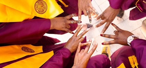 A bunch of hands showing the ASU pitchfork gesture in the center of a circle of people wearing graduation gowns whose faces aren't seen