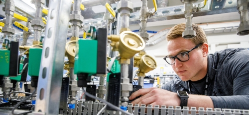 A young man in glasses examines a piece of scientific equipment. The caption reads: Alex Gardeck, a mechanical engineering student, examines one of the precision thermal trim unit water systems that is used to control the temperature of various components
