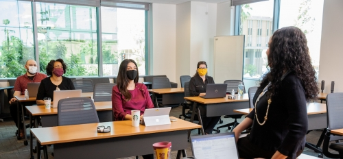 A classroom with four students look to an instructor at the head of the class.