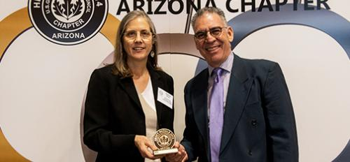 P. Olson and E. Soltero pose with a USGBC Heavy Medal award