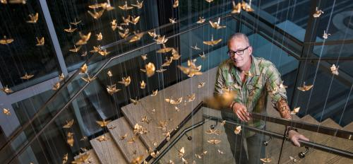 artist posing with art installation of thousands of hanging cranes