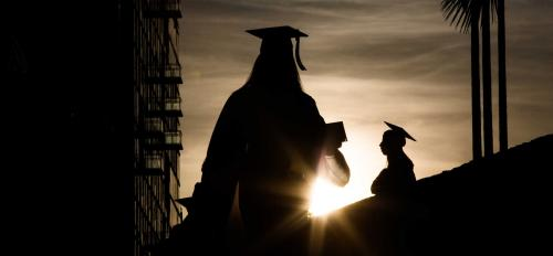Graduates are silhouetted against the setting sun