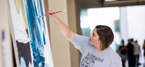 Photo of Heidi Hogden painting a mural at Herberger Institute Day