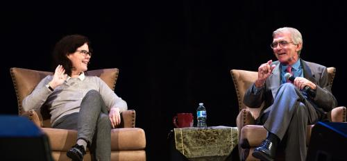 A man and a woman participate in a Hamilton panel onstage